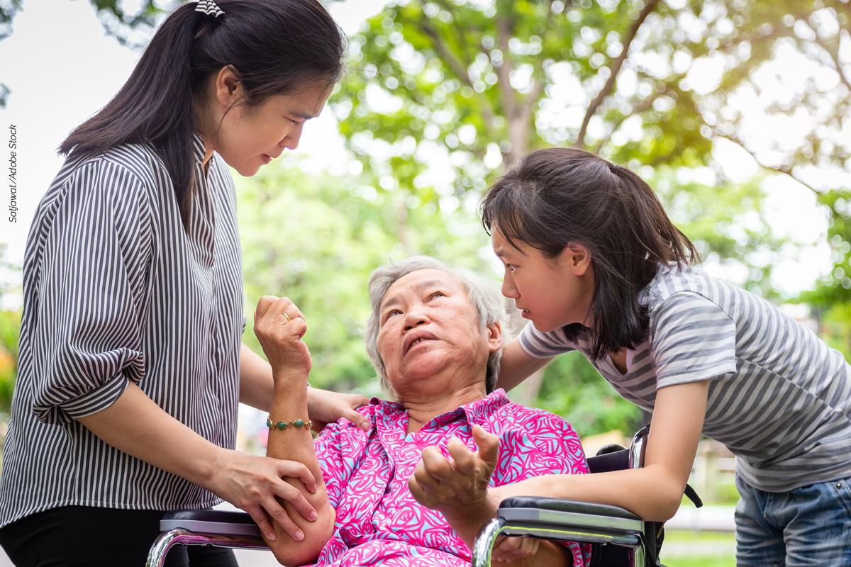 Tipos de epilepsia - senhora paralisada numa cadeira acudida por duas jovens